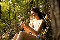 Young woman in forest binding bunch of flowers - MFRF00965
