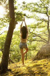 Young woman in forest practicing yoga - MFRF00971