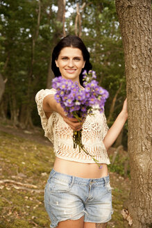 Portrait of smiling young woman with bunch of flowers in forest - MFRF00974