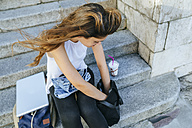 Young woman with laptop and smoothie looking in the backpack - KIJF01664