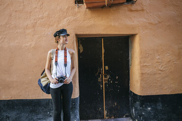 Young woman with camera standing in front of old house - KIJF01670