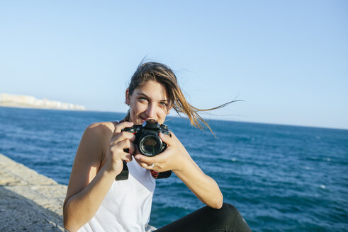 Portrait of smiling young woman with camera at the sea - KIJF01673