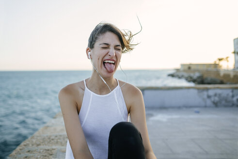 Young woman with earphones making funny faces - KIJF01679
