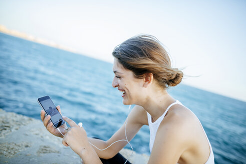 Young woman looking at photos on smartphone at the sea - KIJF01682