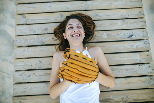 Young woman lying on wooden path laughing with baseball glove - KIJF01691