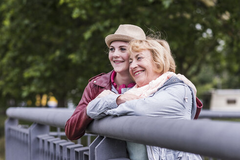 Happy grandmother and granddaughter leaning together on railing - UUF11338