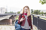 Portrait of smiling young woman looking at cell phone - UUF11344