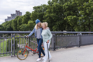 Grandmother and granddaughter strolling on a bridge - UUF11362