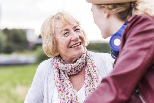 Portrait of happy grandmother talking to her granddaughter - UUF11374