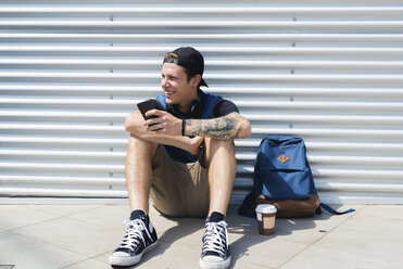 Smiling young man with smartphone, backpack and coffee to go sitting on the ground - FMOF00293