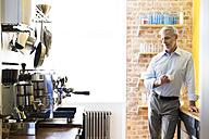 Businessman having coffee break in office kitchen - FKF02450