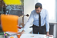 Businessman working at desk in office - FKF02453