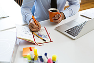Man drawing into notebook at desk in office - FKF02465