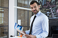 Portrait of confident businessman in creative office - FKF02477