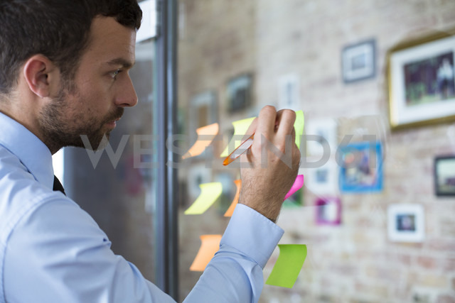 Businessman in office writing on adhesive note on glass wall - FKF02483