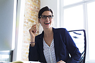 Laughing businesswoman at desk in office - FKF02486