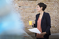 Smiling businesswoman standing in office - FKF02498
