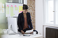 Businesswoman at desk in office looking at printouts - FKF02501