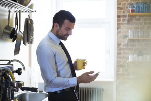 Businessman having coffee break in office kitchen looking at cell phone - FKF02504