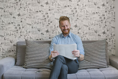Smiling businessman reading newspaper on couch in his living room - MOMF00201
