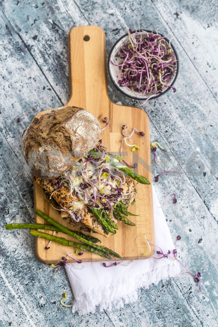 Salmon burger with green asparagus and red cress on chopping board - SARF03345