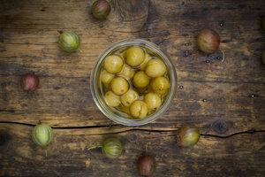 Jar of preserved gooseberries and gooseberries on wood - LVF06266