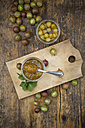 Jar of gooseberry jam, gooseberries and glass of preseved gooseberries on wood - LVF06269