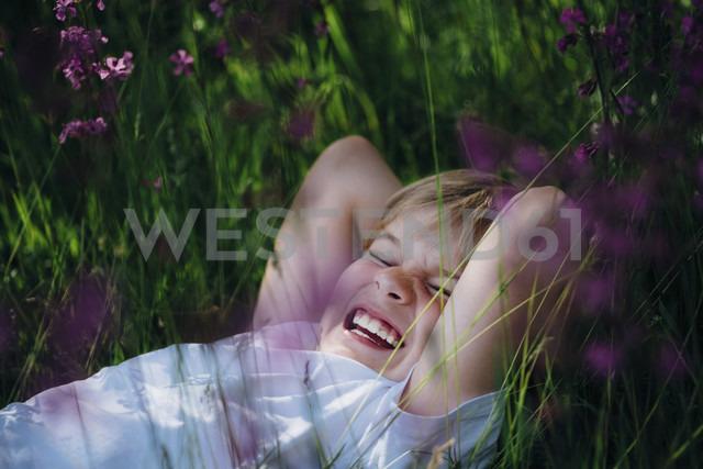 Laughing little boy lying on meadow in the garden - MJF02129