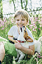 Portrait of smiling little boy sitting with his dog on meadow in the garden - MJF02132