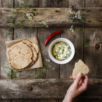 Hand with home-baked Naan bread and bowl of curd dip - EVGF03265
