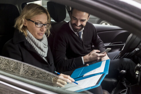 Businessman and businesswoman with documents in car - MAUF01173