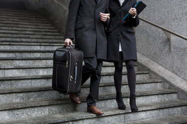 Business couple in the city walking down stairs - MAUF01182