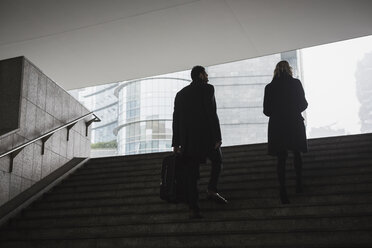 Businessman and businesswoman in the city walking up stairs - MAUF01191