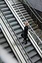 Businesswoman on escalator - MAUF01197