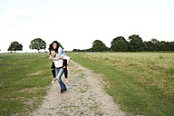 Happy young man giving his girlfriend a piggyback ride - IGGF00047