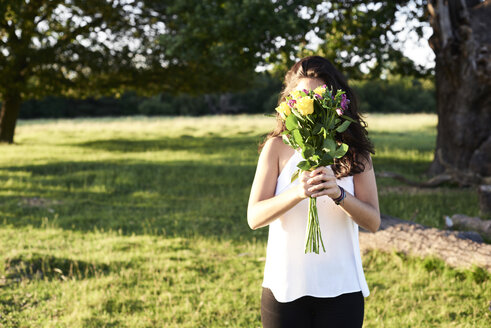 Young woman hiding behind bunch of flower - IGGF00053