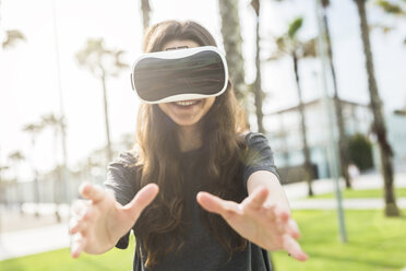 Young woman wearing VR glasses outdoors - GIOF02980