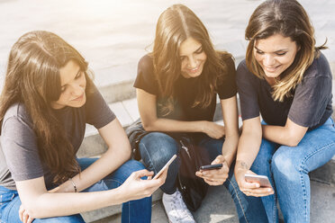 Three smiling young women sitting outdoors looking at cell phones - GIOF02983