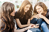 Three happy young women sitting outdoors looking at cell phone - GIOF02986