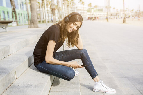 Smiling young woman sitting on steps listening to music - GIOF02992