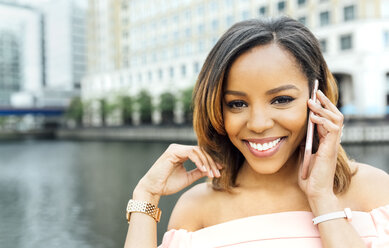 Portrait of smiling woman talking on the phone in the city - MGOF03458