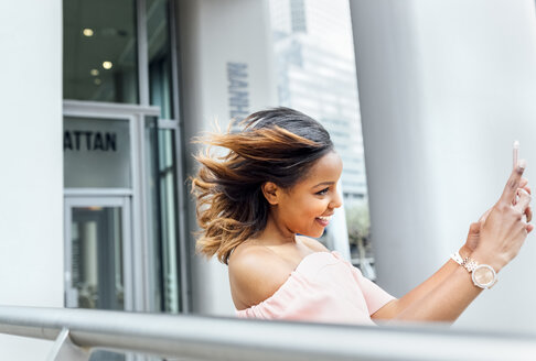 Smiling woman taking a selfie in the city - MGOF03464