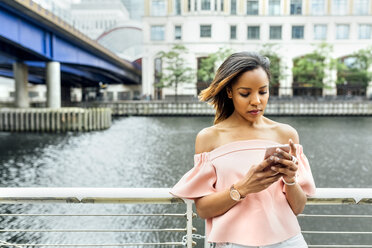 Woman sending messages with her smartphone in the city - MGOF03467