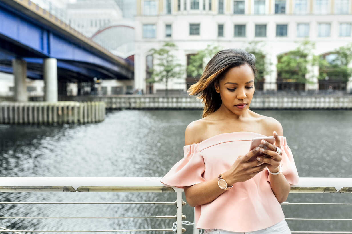 Woman sending messages with her smartphone in the city - MGOF03467 - Marco Govel/Westend61