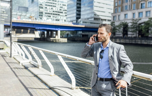 Businessman talking on the phone in the city - MGOF03470