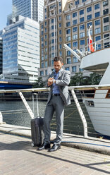 Businessman checking the time in the city - MGOF03473