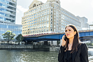 Businesswoman talking on the phone in the city - MGOF03476