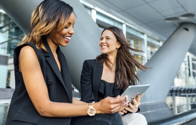 Two happy businesswomen using a tablet in the city - MGOF03479