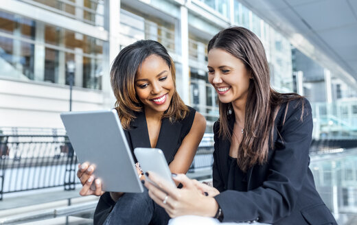 Two businesswomen working with smartphone and tablet in the city - MGOF03482