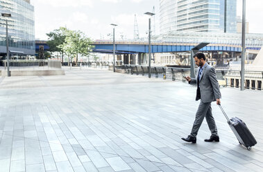 Businessman walking through the city with rolling suitcase and cell phone - MGOF03485